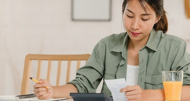 A happy woman sits at her desk filling out her taxes.